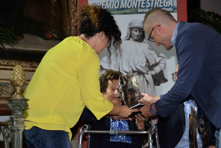 Anna Manelli, accompagnata dalla nipote Katia , riceve il premio dal vice-sindaco di Arcevia F. Quajani